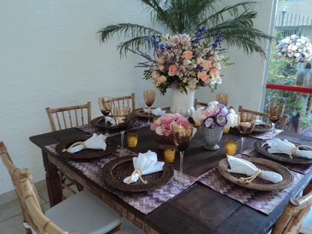 Mesa bem decorada com estilo rústico e flores brancas, rosas, rosa chá e lilás.